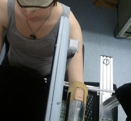 Participant seated in the experimental apperatus. Visible are the leather sleeve and metal occluder positioned on the participant's left forearm. The skin on either side of the metal occluder was brushed (not pictured), and the effect this had on touch localization was assessed by participants pointing on a digitizing table (gray divider between the subject's body and left arm) where they felt the tactile target.