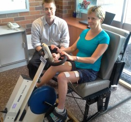 Dr Fornusek and a participant with MS prepare to begin a session of electrical stimulation cycling.